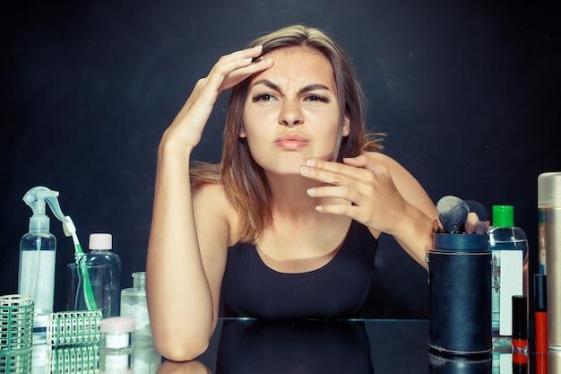 Unzufriedene unglückliche junge frau, die ihr selbst im spiegel auf schwarzem studiohintergrund betrachtet. problem haut und akne konzept. morgen, make-up und menschliche emotionen konzepte