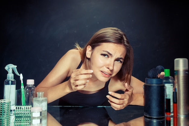 Unzufriedene unglückliche junge frau, die ihr selbst im spiegel auf schwarzem studiohintergrund betrachtet. problem haut und akne konzept.
