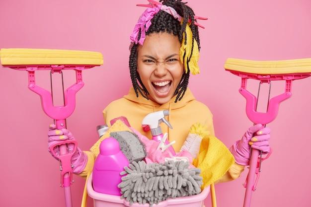 Unzufriedene verärgerte dunkelhäutige junge frau, die mit reinigungsservice beschäftigt ist, hält zwei mopps