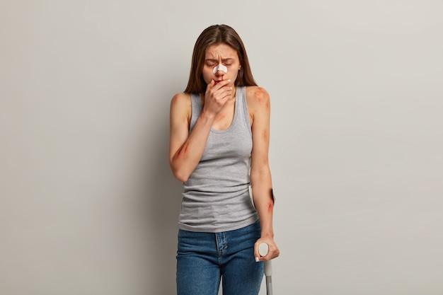 Unzufriedene verletzte frau mit verschiedenen hämatomen, sieht sich traumatischen erfahrungen gegenüber
