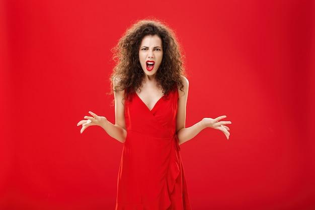 Unzufriedene, wütende und angepisste attraktive lockige frau in stilvollem rotem kleid, die streitet und die stirn runzelt...