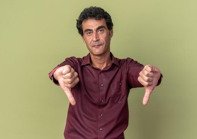 Unzufriedener älterer mann in violettem hemd, der in die kamera schaut und daumen nach unten zeigt, die über grün stehen
