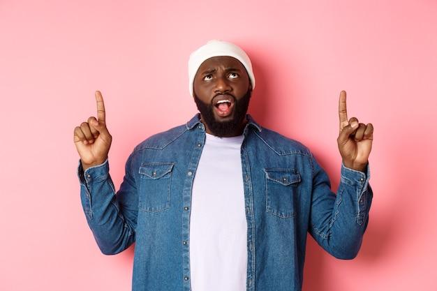 Unzufriedener afroamerikaner in mütze, der mit den fingern nach oben zeigt und in die kamera starrt, sich beschwert, über rosafarbenem hintergrund steht.