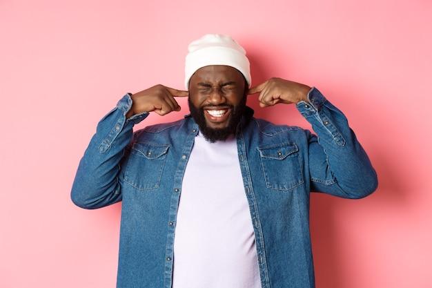 Unzufriedener afroamerikanischer mann verschließt die ohren und verzieht das gesicht vor lautem schrecklichem lärm, stört durch nerviges geräusch, steht auf rosa hintergrund