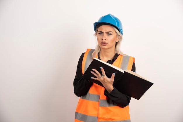 Unzufriedener arbeiter mit notizbuch, das auf weißem hintergrund steht. hochwertiges foto