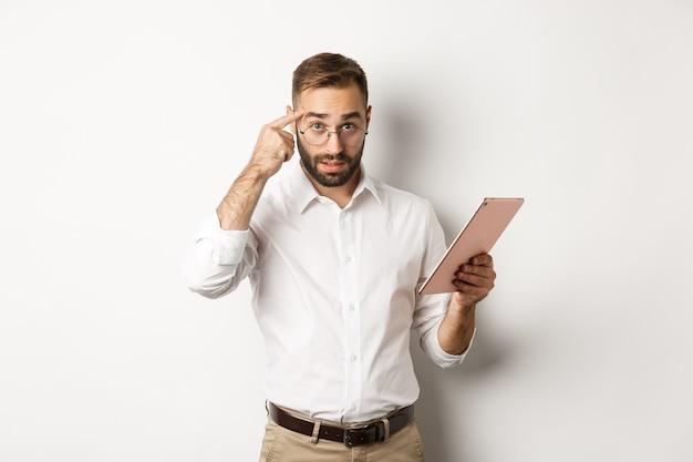 Unzufriedener arbeitgeber schimpft mit mitarbeitern, während er den bericht auf dem digitalen tablet überprüft, auf den kopf zeigt und enttäuscht aussieht und steht