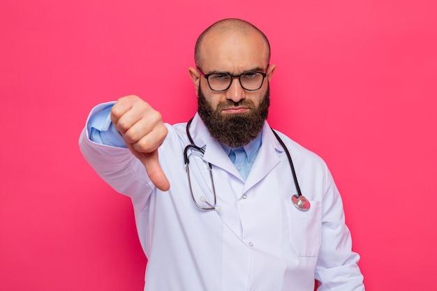 Unzufriedener bärtiger arzt im weißen kittel mit stethoskop um den hals, der eine brille trägt und mit stirnrunzelndem gesicht den daumen nach unten zeigt