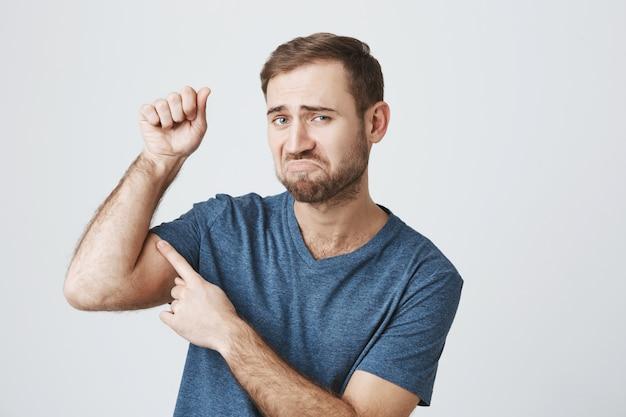 Unzufriedener bärtiger kerl beugt schwachen bizeps, muss ins fitnessstudio gehen