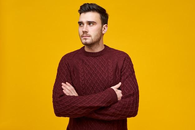 Unzufriedener ernsthafter junger brünetter kerl in stilvollem strickpullover posiert und verschränkt die arme auf seiner brust