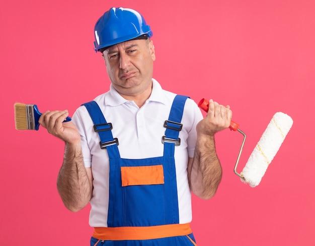 Unzufriedener erwachsener kaukasischer baumeistermann in der uniform hält pinsel und walzenpinsel auf rosa