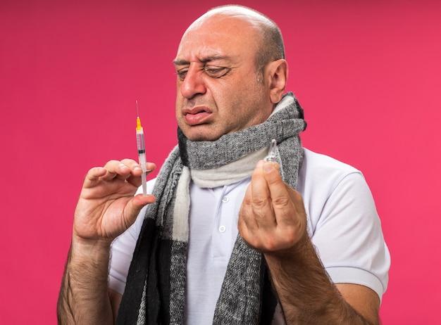 Unzufriedener erwachsener kranker kaukasischer mann mit schal um den hals, der ampulle hält und spritze einzeln auf rosa wand mit kopienraum betrachtet