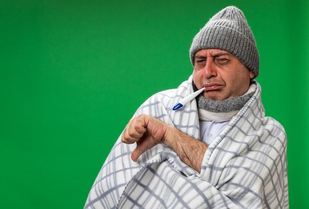 Unzufriedener erwachsener kranker kaukasischer mann mit schal um den hals, der eine wintermütze trägt, die in karierte daumen gewickelt ist und das thermometer im mund isoliert auf grüner wand mit kopienraum hält