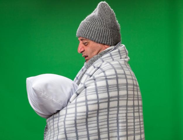 Unzufriedener erwachsener kranker kaukasischer mann mit schal um den hals, der eine wintermütze trägt, die in kariertes halten gewickelt ist und das kissen isoliert auf grüner wand mit kopienraum betrachtet