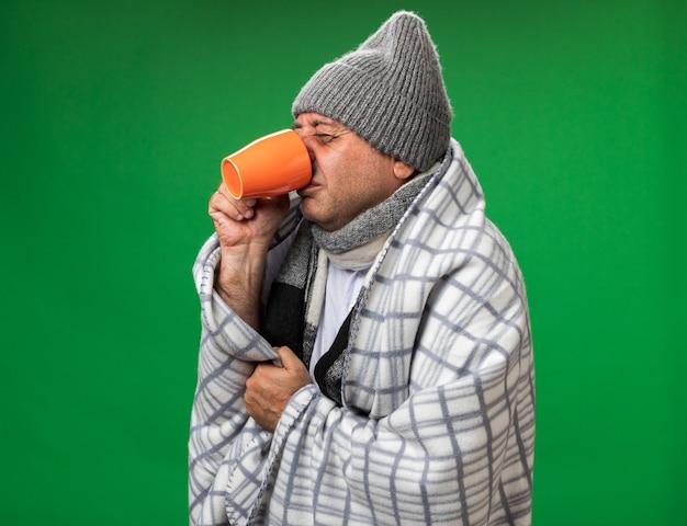 Unzufriedener erwachsener kranker kaukasischer mann mit schal um den hals, der eine wintermütze trägt, die in plaid eingewickelt ist und aus einer tasse isoliert auf grüner wand mit kopierraum trinkt