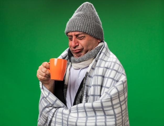 Unzufriedener erwachsener kranker kaukasischer mann mit schal um den hals, der eine wintermütze trägt, die in plaid gehüllt ist und die tasse isoliert auf grüner wand mit kopienraum betrachtet