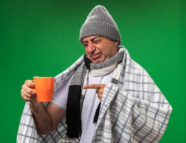 Unzufriedener erwachsener kranker kaukasischer mann mit schal um den hals, der eine wintermütze trägt, die in plaid gewickelt ist und auf die tasse isoliert auf grüner wand mit kopierraum zeigt