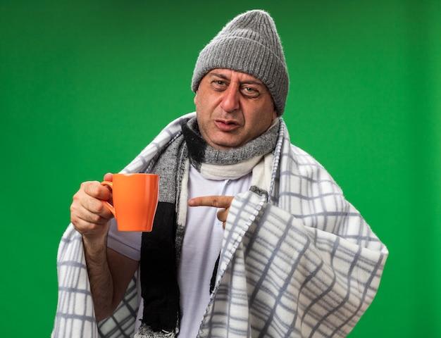 Unzufriedener erwachsener kranker kaukasischer mann mit schal um den hals, der eine wintermütze trägt, die in plaid gewickelt ist und auf die tasse zeigt, die auf grüner wand mit kopienraum isoliert ist