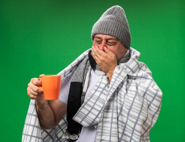 Unzufriedener erwachsener kranker kaukasischer mann mit schal um den hals, der eine wintermütze trägt, die mit der hand in eine plaid-schließnase gewickelt ist und die tasse isoliert auf grüner wand mit kopierraum betrachtet