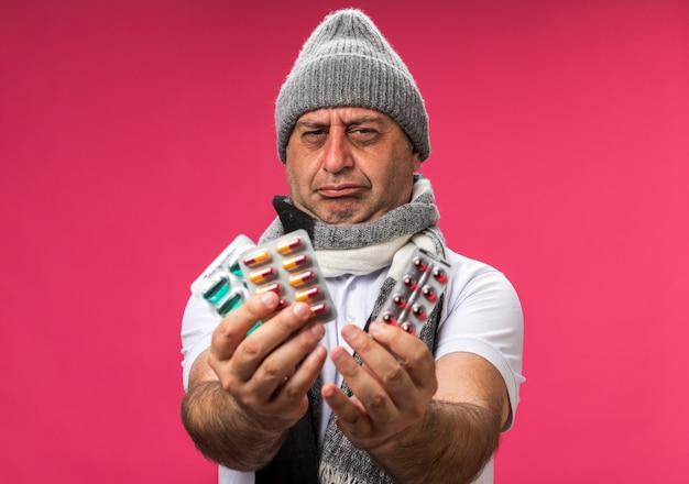 Unzufriedener erwachsener kranker kaukasischer mann mit schal um den hals, der eine wintermütze trägt, die verschiedene medikamentenpackungen isoliert auf rosa wand mit kopierraum hält