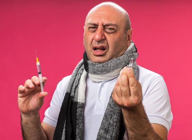 Unzufriedener erwachsener kranker kaukasischer mann mit schal um hals, der spritze und ampulle hält, isoliert auf rosa wand mit kopienraum