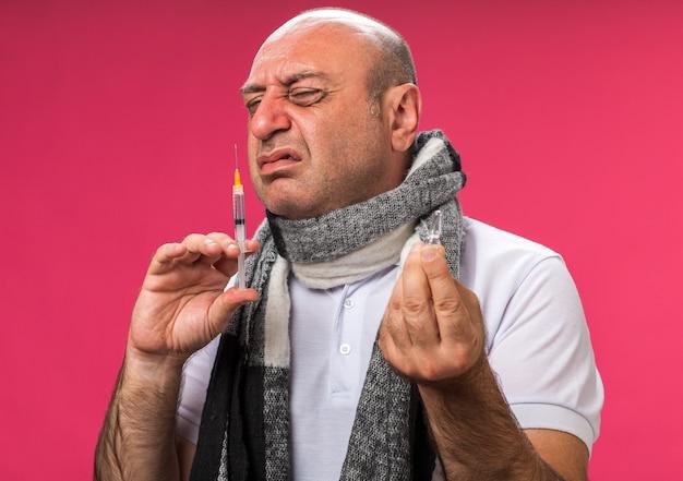 Unzufriedener erwachsener kranker kaukasischer mann mit schal um hals hält ampulle und schnüffelspritze lokalisiert auf rosa wand mit kopienraum