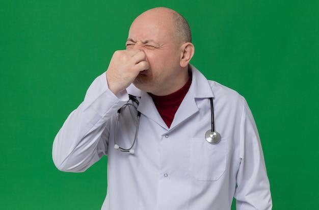 Unzufriedener erwachsener mann in arztuniform mit stethoskop, das seine nase schließt