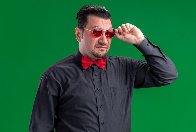 Unzufriedener erwachsener slawischer mann, der seine rote sonnenbrille hält und in die kamera schaut