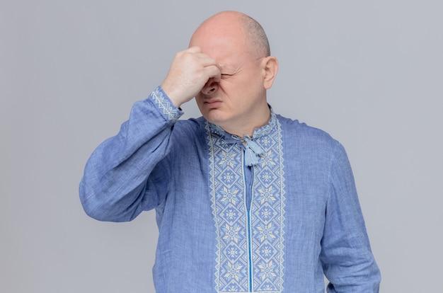 Unzufriedener erwachsener slawischer mann im blauen hemd, der hand auf seine nase legt