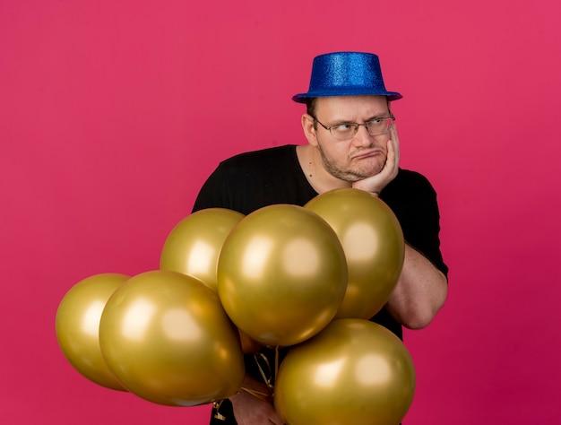 Unzufriedener erwachsener slawischer mann in optischer brille, der eine blaue partyhut-eiterhand am kinn trägt und heliumballons auf der seite hält