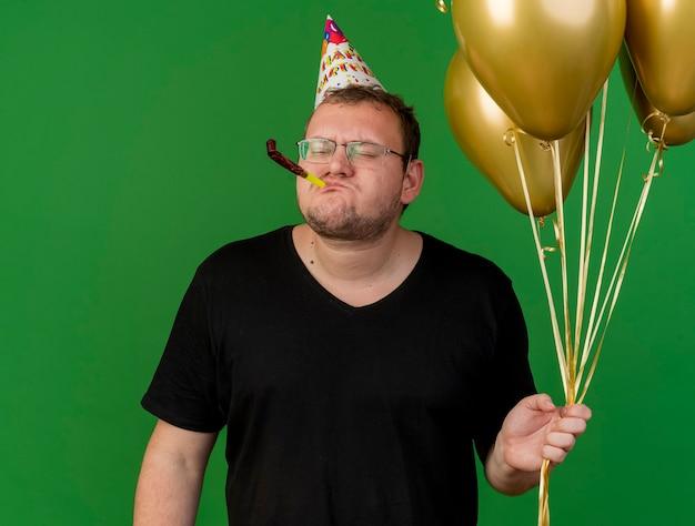 Unzufriedener erwachsener slawischer mann in optischer brille mit geburtstagsmütze hält heliumballons, die partypfeife blasen