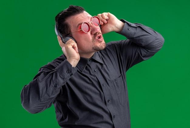 Unzufriedener erwachsener slawischer mann in roter sonnenbrille, der kopfhörer hält und aufschaut