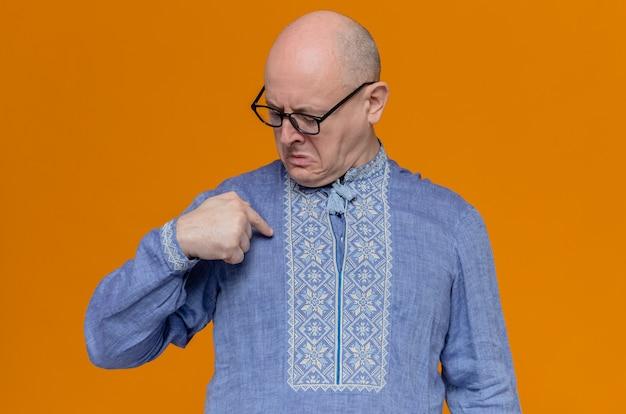 Unzufriedener erwachsener slawischer mann mit optischer brille, der auf sein blaues hemd schaut und zeigt