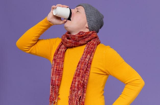 Unzufriedener erwachsener slawischer mann mit wintermütze und schal um den hals, der aus pappbecher trinkt