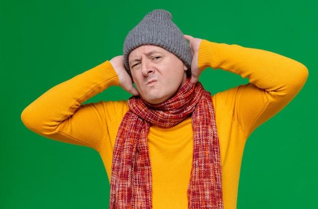 Unzufriedener erwachsener slawischer mann mit wintermütze und schal um den hals, der die hände auf den kopf legt und schaut