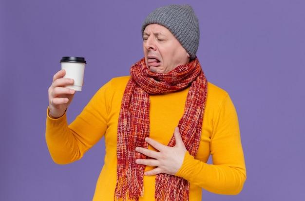 Unzufriedener erwachsener slawischer mann mit wintermütze und schal um den hals, der pappbecher hält und betrachtet