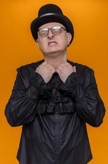 Unzufriedener erwachsener slawischer mann mit zylinder und brille, der den kragen seines schwarzen gothic-hemdes zieht
