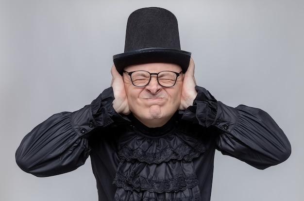 Unzufriedener erwachsener slawischer mann mit zylinder und optischer brille in schwarzem gothic-hemd, der seine ohren mit den händen schließt