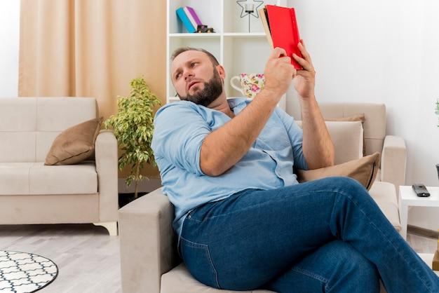 Unzufriedener erwachsener slawischer mann sitzt auf sessel, hält buch und schaut zur seite im wohnzimmer