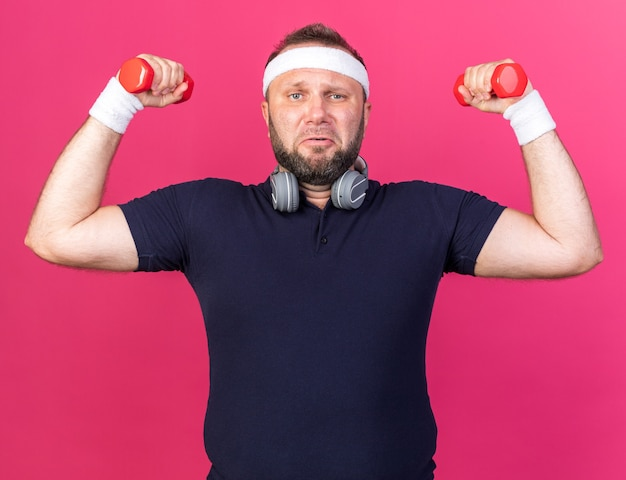 Unzufriedener erwachsener slawischer sportlicher mann mit kopfhörern mit stirnband und armbändern, die hanteln isoliert auf rosa wand mit kopierraum halten