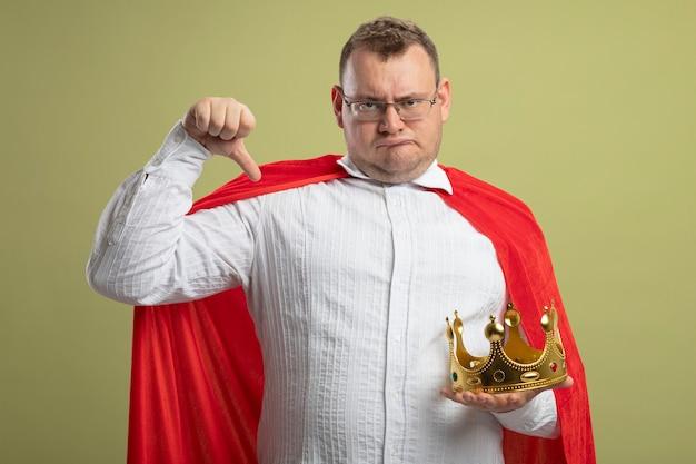 Unzufriedener erwachsener slawischer superheldenmann im roten umhang, der brille und krone trägt, die kamera zeigt daumen unten isoliert auf olivgrünem hintergrund
