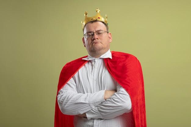 Unzufriedener erwachsener slawischer superheldenmann im roten umhang, der brille und krone trägt, die mit geschlossener haltung stehen, die auf olivgrüner wand mit kopienraum isoliert wird
