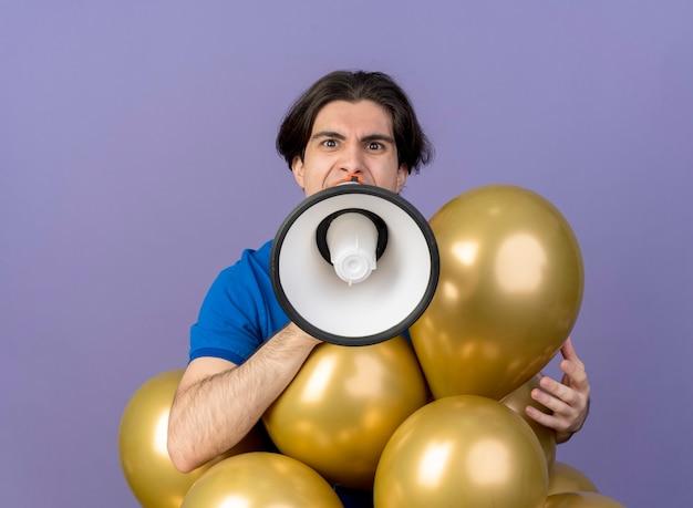 Unzufriedener gutaussehender kaukasischer mann steht mit heliumballons, die in den lautsprecher schreien