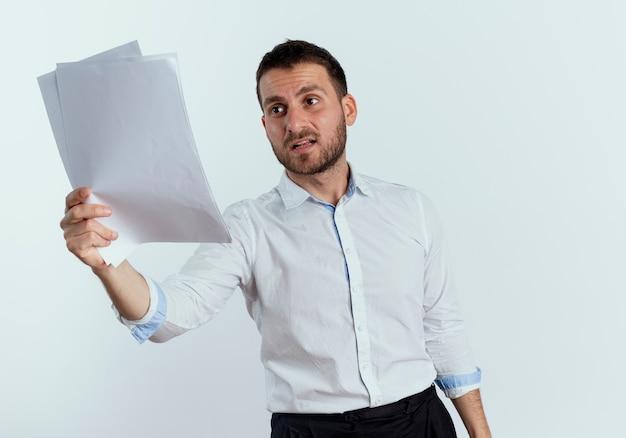 Unzufriedener gutaussehender mann hält und betrachtet papierblätter, die auf weißer wand isoliert werden
