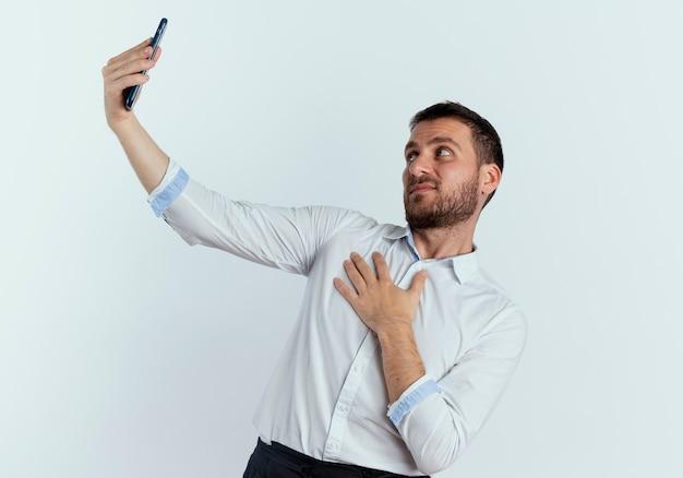 Unzufriedener gutaussehender mann legt hand auf brust und betrachtet telefon lokalisiert auf weißer wand