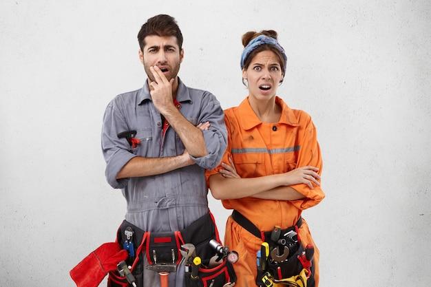 Unzufriedener handwerker und seine partnerin schauen sich das objekt an, das sie reparieren sollten, erkennen alle schwierigkeiten,