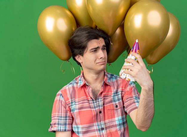 Unzufriedener hübscher kaukasischer mann steht vor heliumballons, die geburtstagskappe halten und betrachten and