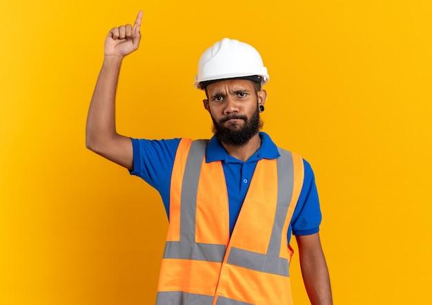 Unzufriedener junger afroamerikanischer baumeister in uniform mit schutzhelm, der nach oben zeigt, isoliert auf orangefarbenem hintergrund mit kopierraum