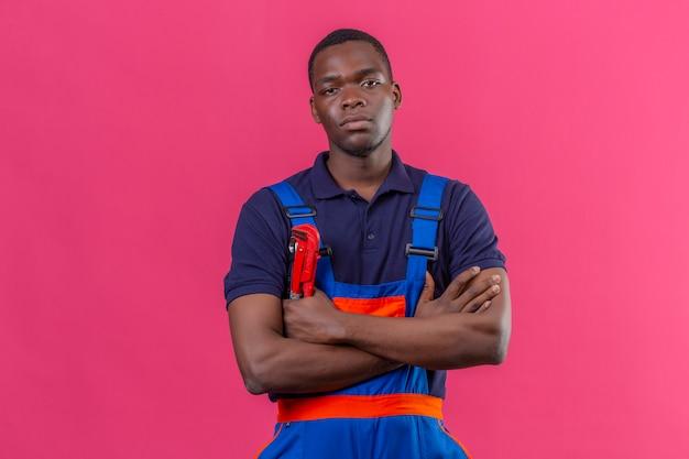 Unzufriedener junger afroamerikanischer baumeistermann, der bauuniform und mütze trägt, die mit verschränkten armen auf brust mit unglücklichem gesicht auf rosa stehen