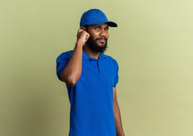 Unzufriedener junger afroamerikanischer lieferbote, der sein ohr mit dem finger schließt, isoliert auf olivgrünem hintergrund mit kopierraum
