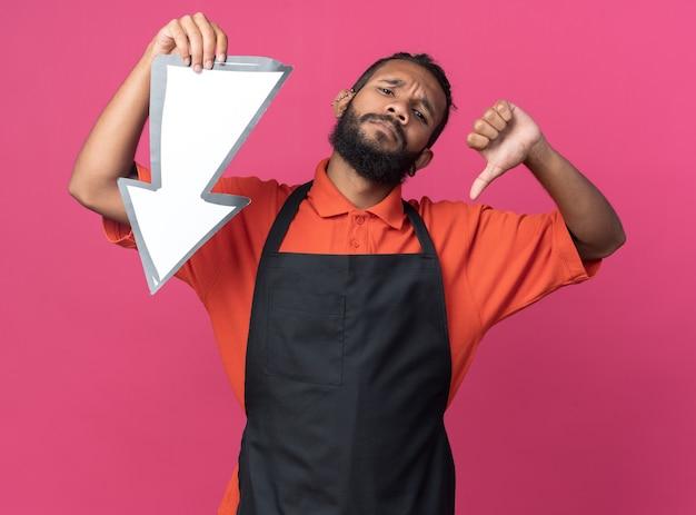 Unzufriedener junger afroamerikanischer männlicher friseur, der uniform hält, die pfeilmarkierung hält, die nach unten zeigt und kamera betrachtet daumen unten auf rosa hintergrund zeigt